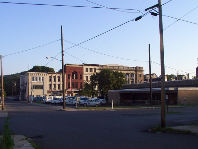 A sunset view of Independence St., south from Washington St. Rear of post office is in foreground; far right, the American Legion building, which houses the library. The brick building is the Llwellyn Building--after David Llwellyn, I presume.